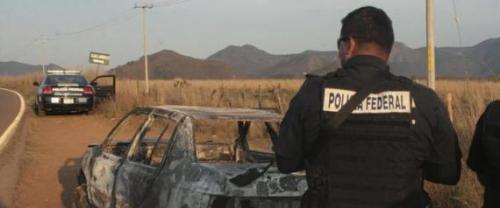 Federal police stand next to a bullet riddled and burned car after a criminal gang ambushed a police convoy near the town of Soyatlan, near Puerto Vallarta, Mexico, Monday, April 6, 2015. According to the Jalisco state prosecutors office, at least 15 state policed officers were killed and five others wounded, the single deadliest attack on Mexican police in recent memory. (ANSA/AP Photo)