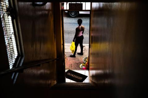 Vista da dentro di un hotel che affaccia sulla strada dove si vede una donna afrodiscendente e uno zerbino con la scritta welcome