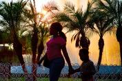 Una donna afrodiscendente passa insieme a suo figlio davanti a una fontana con delle palme