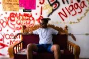 un uomo con occhiali da sole seduto su un divano con dietro delle scritte sul muro