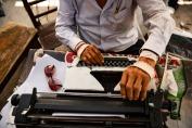 un uomo scrive su una macchian da scrivere con le mani coperte da bene e ferite