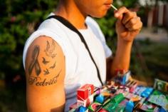 un ragazzo vende prodotti in strada mentre mangia un lecca lecca e mostra il suo tatuaggio sulla spalla