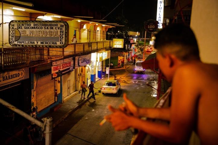 vista dal balcone che affaccia su una strada di Tapachula con un ragazzo a petto nudo che fuma